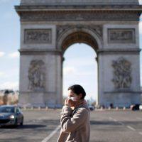 Uma mulher usando uma máscara protetora caminha perto do Arco do Triunfo enquanto a França enfrenta um surto de doença por coronavírus (COVID-19), em Paris