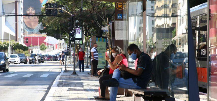 Usuários de transporte público usam máscaras de proteção contra covid-19 em ponto de ônibus na rua da Consolação